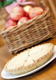 Apple pie on a wooden table. With a basket of apples in background Royalty Free Stock Photo