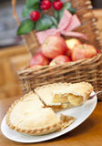 Apple pie on a wooden table. With a basket of apples in background Stock Photo