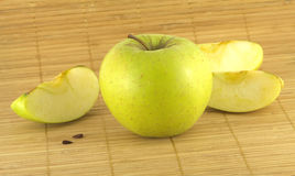 Apple with pieces on wicker mat Royalty Free Stock Images