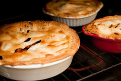 Three apple pies cooking in the oven stock photo