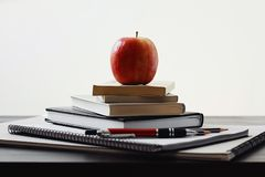 Apple, pile of books and school supplies on the table stock photos