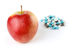 An Apple and a Pile of Medication Pills Royalty Free Stock Photography