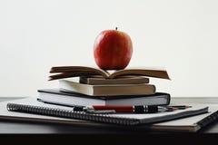 Apple, pilha dos livros e das fontes de escola na tabela imagem de stock
