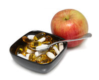 Apple and Pills. Fuji Apple and various pills in black bowl on white background Royalty Free Stock Photo