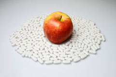 Apple and Pills. Red apple with more pills on the table Royalty Free Stock Images