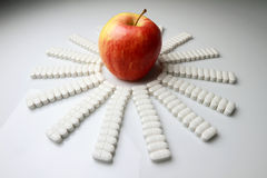 Apple and Pills. Red apple with more pills on the table Royalty Free Stock Photography