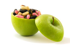 Apple with pills. Green apple filed with colourful pills, isolated on white background Royalty Free Stock Images