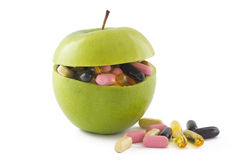 Apple with pills. Green apple filed with colourful pills, on white background Royalty Free Stock Photo