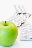 Apple and pills. Green apple and pills isolated stock photography