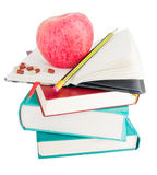 Apple and pills on big pile of books. Apple with pills and pencil on textbook heap as ways to stimulate memory Stock Images