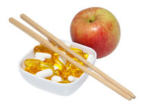 Apple with pills and chopsticks. On white background Stock Image