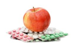 Apple with pills  isolated over white Royalty Free Stock Images