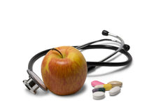 Apple with pills and a stethoscope Royalty Free Stock Photo