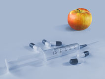 Apple or pills and syringe. Apple (colored) or pills and syringe (monochromatic Royalty Free Stock Photography