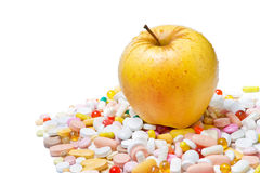 Apple and pills on white background Royalty Free Stock Images
