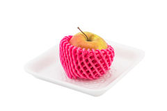 Apple with pink foam net protection on foam tray isolated white Royalty Free Stock Photo