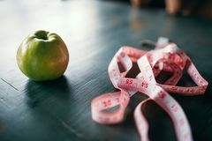 Apple and pink measuring tape, weight loss concept. Apple and pink measuring tape on wooden table closeup. Weight loss diet concept, fat or calories burning Royalty Free Stock Photography