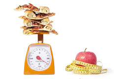 Apple and Pizza Slilces. Photo of pizza slices stacked on a scale with an Apple isolated over white Stock Photos