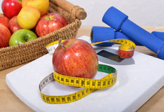 Apple placed on a scales,. Apple placed on a scales and free weights Stock Photography