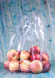 Apple in plastic bag. On wood stock photography