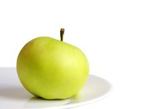 Apple on plate. A ripe green apple on white plate and isolated on the white background Stock Photo