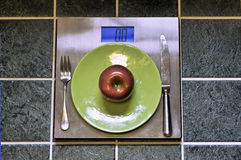 Apple and Plate atop Weight Scale Stock Image