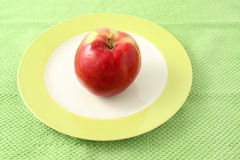 Apple in plate on a green cloth background Stock Images