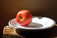 Apple on the plate. Red juicy Apple on a white plate Royalty Free Stock Image