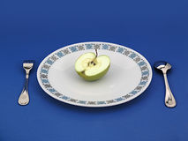 Apple on plate with silverware. Half of a green apple on a dinner plate with a fork and spoon against a blue background royalty free stock images