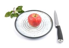 Apple on plate and white. Colorful and crisp image of apple on plate and white Royalty Free Stock Photo