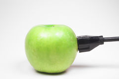 Apple plugged in. A green apple with electrical plug Stock Photos