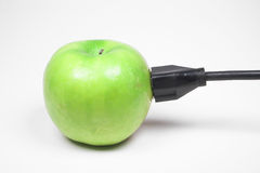 Apple plugged in. A green apple with electrical plug Royalty Free Stock Photo