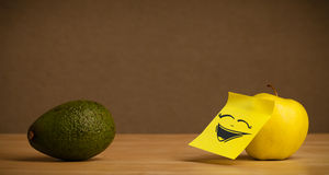 Apple with post-it note laughing on avocado Stock Photography