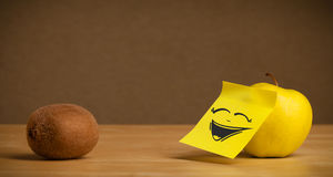 Apple with post-it note laughing on kiwi Stock Images