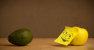 Apple with post-it note looking curiously at avocado Stock Photos