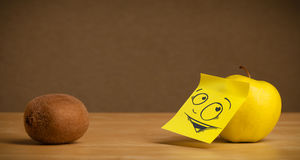 Apple with post-it note looking curiously at kiwi Royalty Free Stock Photo