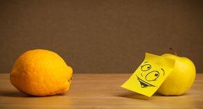 Apple with post-it note looking curiously at lemon Royalty Free Stock Image