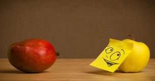 Apple with post-it note looking curiously at mango Stock Photo