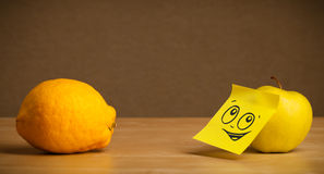 Apple with post-it note looking at lemon Stock Images