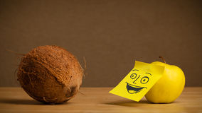 Apple with post-it note smiling at coconut Stock Photo