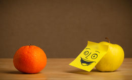 Apple with post-it note smiling at orange Royalty Free Stock Photography