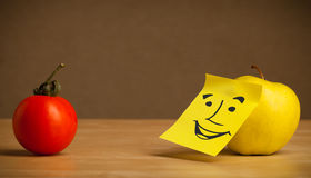 Apple with post-it note smiling at tomato Royalty Free Stock Image