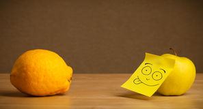 Apple with post-it note sticking out tongue to lemon Stock Image
