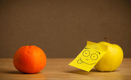 Apple with post-it note sticking out tongue to orange Stock Image