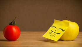 Apple with post-it note sticking out tongue to tomato Stock Image