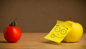 Apple with post-it note sticking out tongue to tomato Stock Images