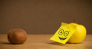 Apple with post-it note watching at kiwi Royalty Free Stock Photo