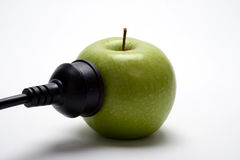 Apple powered. Green apple powering the market. Metaphor for computer and phone manufacturer dominating stock photos