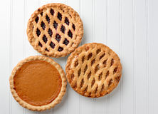 Apple Pumpkin Cherry Pies. High angle shot of three pies, apple, pumpkin, and cherry. Horizontal format on a white beadboard surface. Thes pies are favorites for Royalty Free Stock Photography