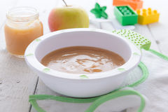 Apple puree in bowl and bib on white table Stock Image